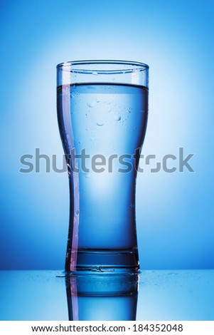 glass of water on blue background - stock photo