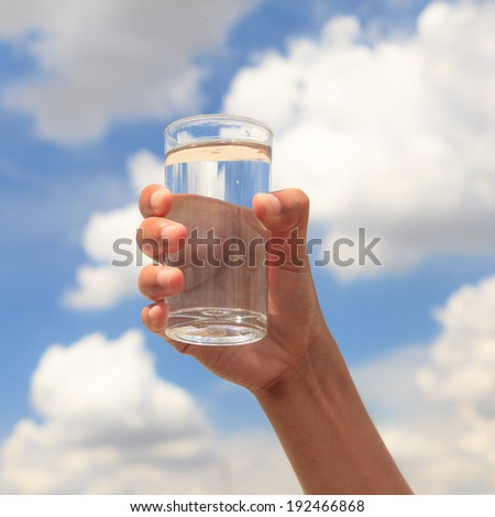 Glass of water on blue sky - stock photo