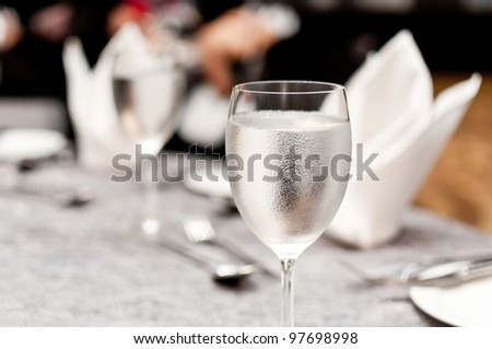 Glass of water on luxury table setting for dining - stock photo