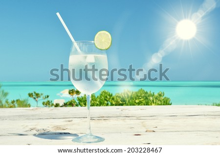 Glass of water on the tropical beach