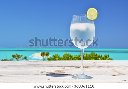 Glass of water on the tropical beach - stock photo