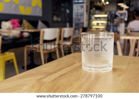 glass of water on wooden table in cafe
