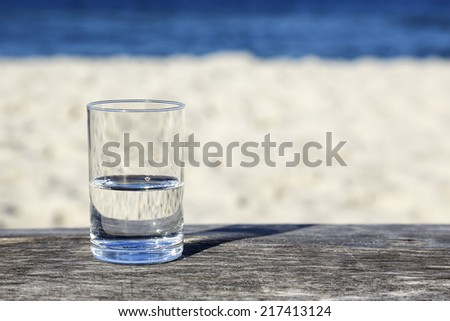 Glass of water which is half-full stands on a wooden table which stands on the sand beach by the sea - stock photo