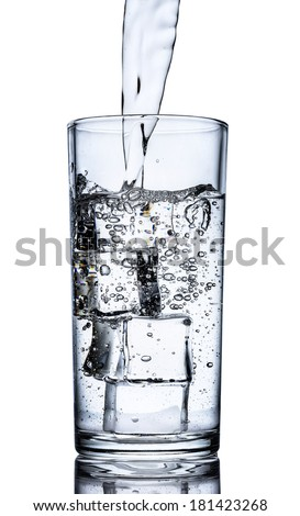 Glass of water with a splash and ice cubes  - stock photo