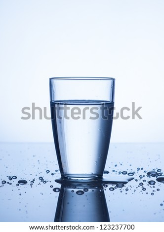 Glass of water  with drops on light background - stock photo