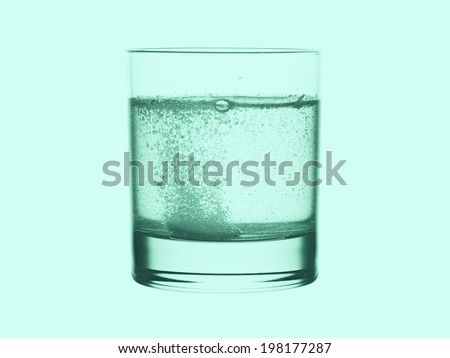Glass of water with effervescent tablet in green tone