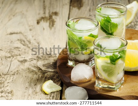 Glass of water with fresh lemon, ice and mint, selective focus - stock photo