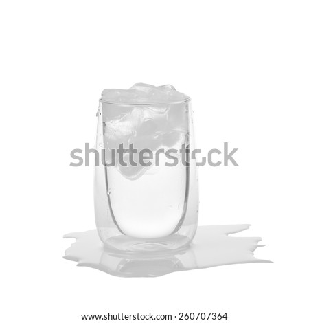 Glass of water with ice and puddle underneath isolated on white background - cooling, freshness and quenching thirst concept - stock photo