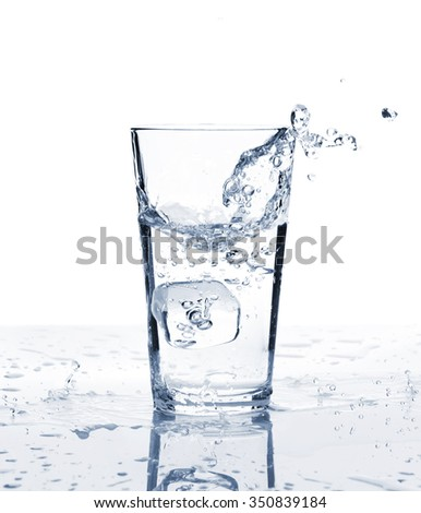 Glass of water with ice and splash. Isolated on white background