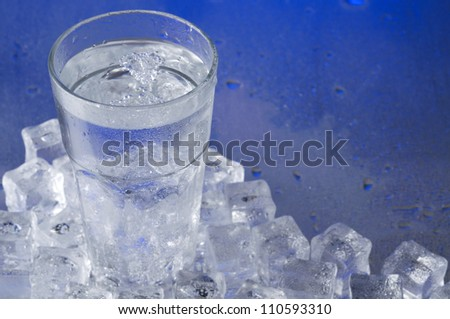 Glass of water with ice cubes over blue background - stock photo