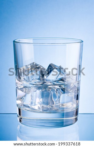 Glass of water with ice on a blue background - stock photo