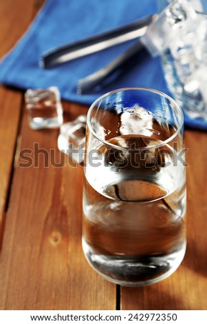 Glass of water with ice on napkin on wooden table background - stock photo