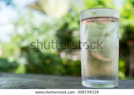 Glass of water with ice on the table dark wood - stock photo