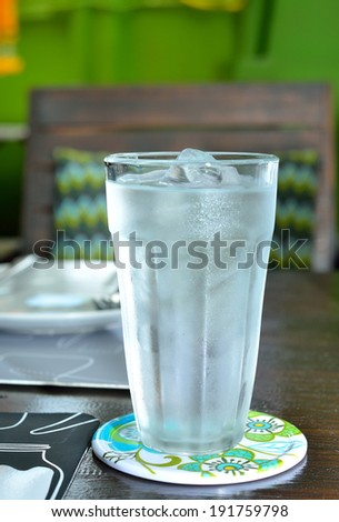 glass of water with ice on wooden table. - stock photo