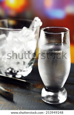 Glass of water with ice on wooden table and bright blurred background - stock photo