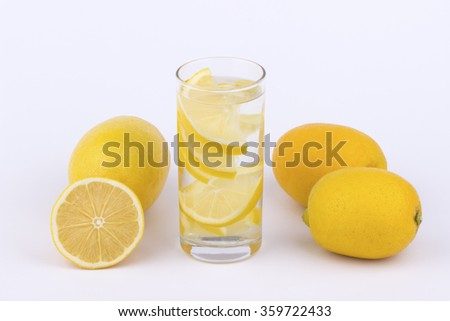 Glass of water with lemon slices and lemons on white background.
