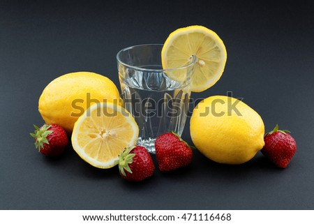 Glass of water with lemon surrounded by lemons and strawberries on black background