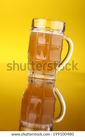 Glass of wheat beer over a brigth yellow background