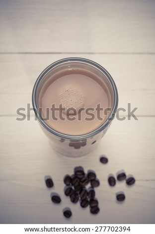 glass of whie coffee  and coffee beans on the wooden background - stock photo