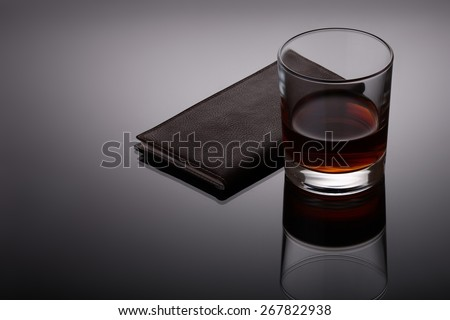 Glass of whiskey and a business card holder on reflective dark background - stock photo