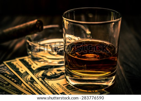 Glass of whiskey and a money with cuban cigar on a wooden table. Angle view, shallow depth of field, focus on the glass of whiskey, image vignetting and the orange-blue toning - stock photo