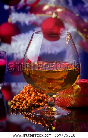glass of whiskey and Christmas gifts and Christmas decoration candles and Christmas tree at the background - stock photo