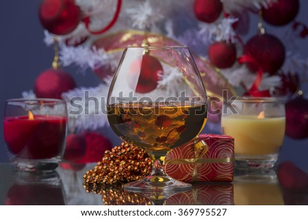 glass of whiskey and Christmas gifts and Christmas decoration candles and Christmas tree at the background