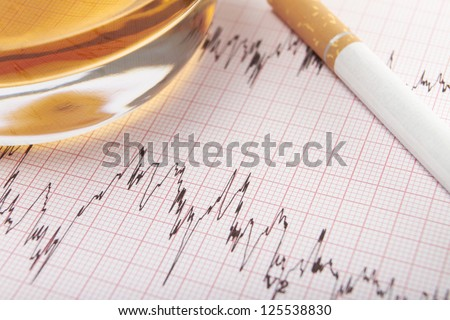 Glass Of Whiskey And Cigarette On ECG Printout - stock photo