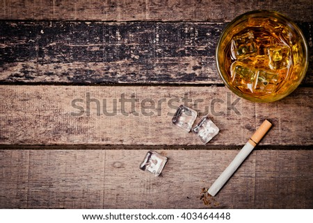 Glass of whiskey and  cigarettes. An old and vintage countertop with highlight and a glass of hard liquor  - stock photo