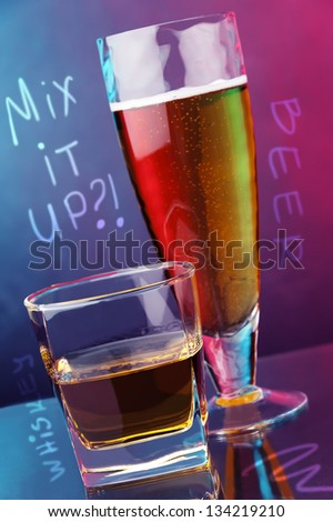 glass of whiskey and glass of beer against two color background - stock photo