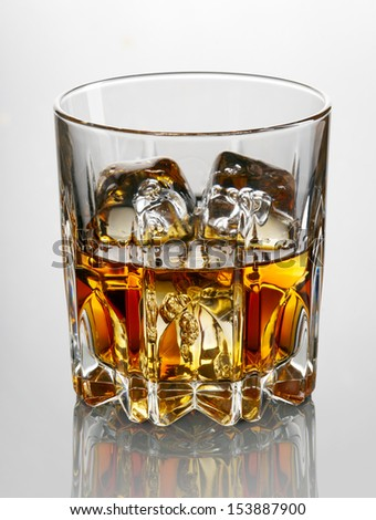 Glass of whiskey and ice - stock photo