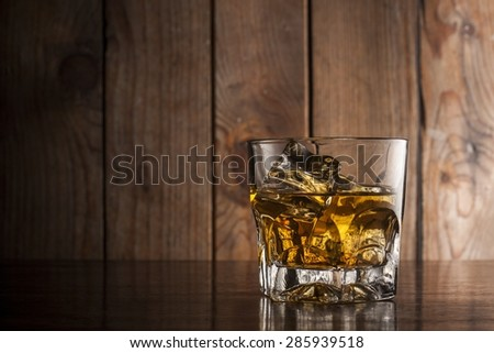 Glass of whiskey and ice cubes on wooden surface - stock photo