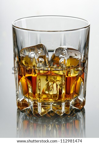 Glass of whiskey and ice  over dark background - stock photo