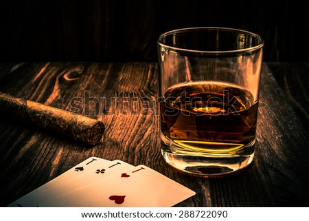 Glass of whiskey and playing cards with cuban cigar on the wooden table. Angle view, image vignetting and the orange-blue toning, identification cards ace Russian letter - stock photo