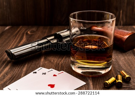 Glass of whiskey and playing cards with revolver on the wooden table. Angle view, identification cards ace Russian letter - stock photo