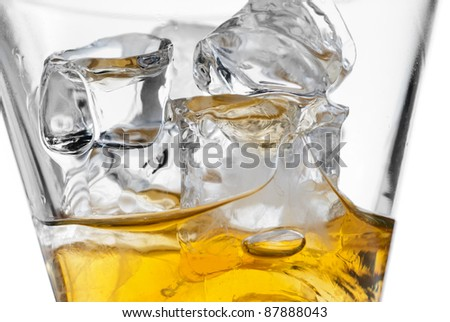 Glass of whiskey closeup of melting ice cubes
