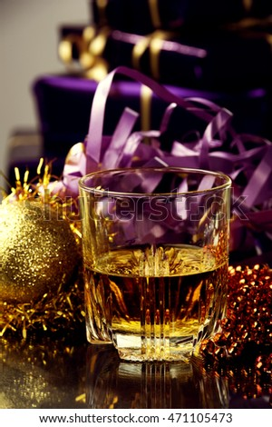Glass of whiskey during Holidays, moment of celebration of Jesus Christ Birth,the moment of a Holiday gifts, joy and celebration time.