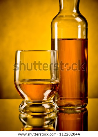 Glass of whiskey next to a bottle of whiskey - stock photo