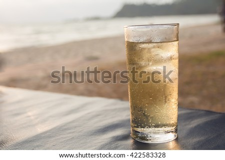 Glass of whiskey on a blurred background of the sea. - stock photo