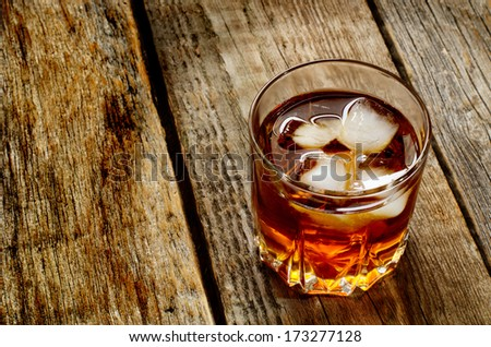 glass of whiskey on a wood background