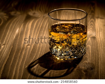 Glass of whiskey on a wooden surface - stock photo