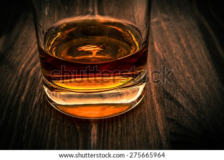 Glass of whiskey on a wooden table. Close up view, image vignetting and the orange-blue toning