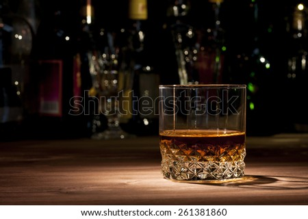 Glass of whiskey on a wooden table in the bar - stock photo
