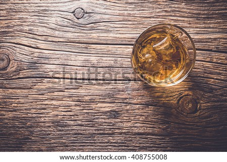 Glass of whiskey on an old wooden table - stock photo