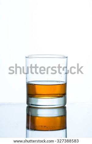 Glass of whiskey on glass table and white background