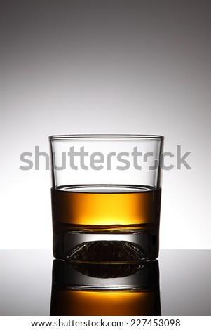 Glass of whiskey on grey background - stock photo