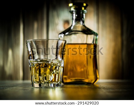 Glass of whiskey on the rocks and a bottle on a wooden background - stock photo