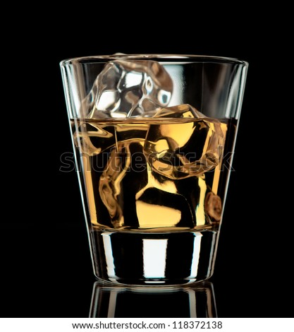 Glass of whiskey on the rocks on black background - stock photo