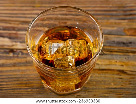 Glass of whiskey on wooden background. Selective focus