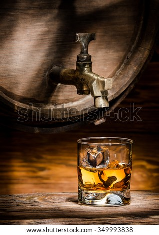 glass of whiskey or brandy ice poured from an old oak barrel - stock photo